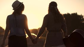 Girlfriend go on the road in the rays of the rising sun and holding hands stock footage
