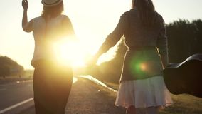 Girlfriend go on the road in the rays of the rising sun and holding hands.  stock footage