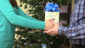 Girlfriend hands give present box for boyfriend on Christmas. Female woman give yellow present gift box with ribbon for boyfriend on Christmas tree background stock video footage