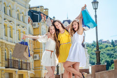Girlfriend happy hug. Three friends holding shopping bags and ra Royalty Free Stock Photos