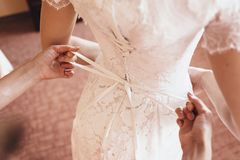 A girlfriend helps the bride to lace her wedding dress stock images