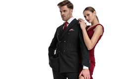 Girlfriend holding his confident boyfriend from behind. Determined boyfriend looking to the side, wearing a black suit, holding one of his hand in his pocket and stock photography