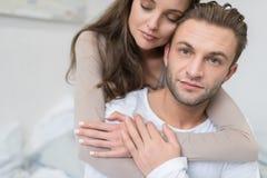 Girlfriend hugging boyfriend from the back. In bedroom stock image