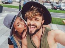 Girlfriend kissing boyfriend while he is taking selfie royalty free stock photo
