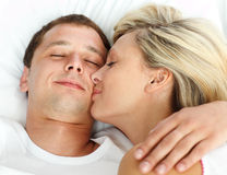 Girlfriend kissing her boyfriend in bed. Close-up of girlfriend kissing her boyfriend in bed Stock Photo
