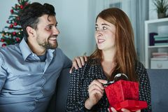 Girlfriend looks sceptical to her christmas gift Royalty Free Stock Images