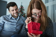 Girlfriend looks sceptical to her christmas gift Royalty Free Stock Photography