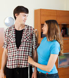 Girlfriend measuring guy with measuring tape Stock Photo