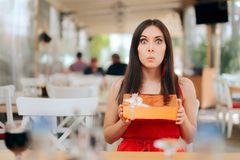 Funny Woman Holding Birthday Gift in a Restaurant royalty free stock image