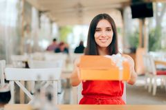 Funny Woman Holding Birthday Gift in a Restaurant royalty free stock photography