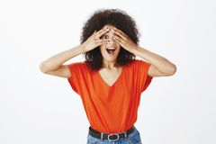 Girlfriend peeking impatiently waiting surprise. Portrait of good-looking happy woman with dark skin and afro hairstyle stock photography