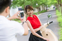 Girlfriend photo shoot. Guy taking a picture of his pretty girlfriend standing by the scooter royalty free stock photo
