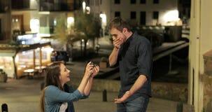 Girlfriend proposing marriage to her boyfriend. Girlfriend proposing marriage to her happy boyfriend in the street stock video