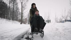 Girlfriend pulling her boyfriend on a sleigh stock video footage