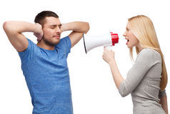 Girlfriend screaming though megaphone at boyfriend. Couple, family and relationship problems concept - girlfriend screaming though megaphone at his boyfriend stock photos