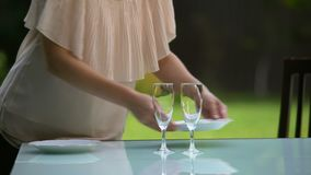 Girlfriend serving plates and wineglasses for date, family dinner outdoors. Stock footage stock footage