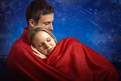 Snuggling cute couple under the blanket. Girlfriend sleeping on her boyfriend arm Stock Photography