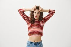 Girlfriend is stubborn like goat when she need something. Funny and emotive slender woman in cropped top frowning while. Making threatening face, holding index Royalty Free Stock Photos