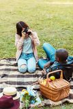 Girlfriend taking photo of her boyfriend stock photography