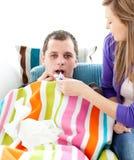Girlfriend taking temperature of her boyfriend Stock Photo