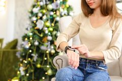 Girlfriend testing smartwatch New Year present in cozy room. Girlfriend get smartwatch from boyfriend as present for New Year, smiling lady sitting in chair stock photos