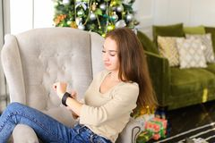Girlfriend testing smartwatch New Year present in cozy room. Girlfriend get smartwatch from boyfriend as present for New Year, smiling lady sitting in chair royalty free stock photos