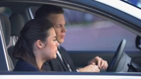 Girlfriend trying to stop man drinking alcohol on driver seat, harmful addiction. Stock footage stock video footage
