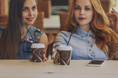 Girlfriend women in a summer cafe with cups of coffee Royalty Free Stock Photos