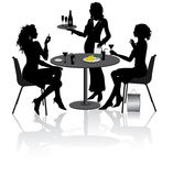 Girlfriends. Two beautiful girlfriends sit and talk in Restaurant Stock Images
