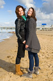 Girlfriends. Two young brunette women on the beach on a beautiful autumn afternoon stock photo