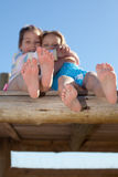 Girlfriends. Close up on feet of little girls hugging and smiling royalty free stock photo