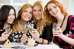Girlfriends. Portrait of four girlfriends holding beverages and looking at camera royalty free stock photos