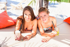 Girlfriends in beach bar drinking cocktails Royalty Free Stock Images