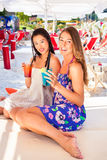 Girlfriends in beach bar drinking cocktails Stock Photos