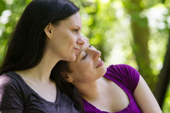 Girlfriends being affectionate in park, horizontal Royalty Free Stock Image