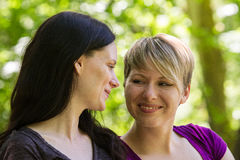 Girlfriends being affectionate in park, horizontal Royalty Free Stock Images