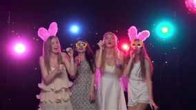 Girlfriends blowing soap bubbles at bachelorette party. Slow motion. Girlfriends at bachelorette party having fun and blowing soap bubbles, against disco lights stock video
