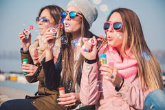 Girlfriends blowing soap bubbles. On a sunny day Royalty Free Stock Image