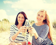 Girlfriends with bottles of beer on the beach Royalty Free Stock Photography