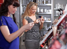 Girlfriends buying and testing cosmetics Royalty Free Stock Image
