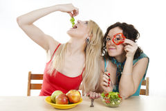 Girlfriends cheerfully play with food. Girlfriends cheerfully play with health food behind a table Stock Images