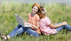 Girlfriends at countryside with laptop Royalty Free Stock Photos
