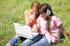 Girlfriends at countryside with laptop Royalty Free Stock Photo