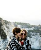 Girlfriends cuddle together under blanket on top of the mountain stock images
