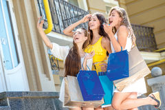 Girlfriends do selfie on a cell phone. Girls holding shopping ba Stock Photo