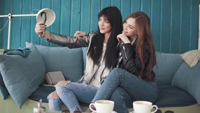 Girlfriends do selfie on mobile phone cameras while sitting in a cafe. two attractive girls take pictures on the camera. Of the smartphone and fool around stock video footage