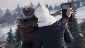 Girlfriends do selfie on the mountain using tablet. Two smiling girlfriends do selfie on the mountain in the winter using digital tablet stock footage