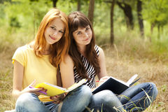 Girlfriends doing homework at the park. Royalty Free Stock Photography