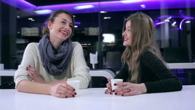 Girlfriends drinking coffee and talking in cafe. Two beautiful girls talking in cafe. Girlfriends drinking coffee and talking in cafe. Girls talking in cafe stock video