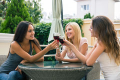 Girlfriends drinking red wine outdoors in the restaurant. Portrait of a happy three girlfriends drinking red wine outdoors in the restaurant Stock Photo
